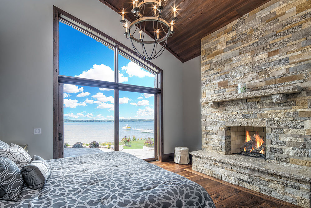 Lake view bedroom with stone fireplace